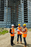 Inspection Visit at Construction Site. Group of three men wearing protective helmets and vests, one of them executive official, explaining project details to stock images
