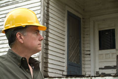 Inspector. A man in a hard hat looking at an old rundown house Royalty Free Stock Image