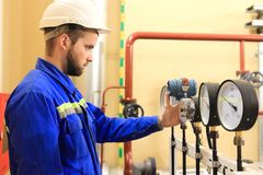 Inspector checking pressure gauges on heating boiler system. Engineer monitors manometers on industrial factory royalty free stock photography
