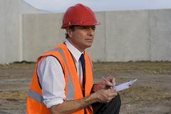 Inspector At Construction Site. Construction inspector wearing safety equipment and holding a clipboard and pen in his hands, looking out at the building site in Royalty Free Stock Images