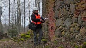 Inspector de construcción con la documentación que comprueba ruinas viejas metrajes