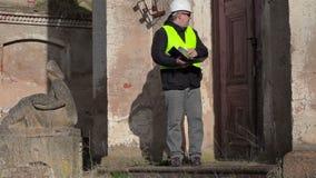 Inspector de construcción que comprueba la documentación cerca de puerta del edificio almacen de metraje de vídeo