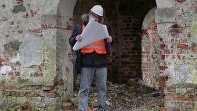 Inspector de construcción que comprueba la documentación en las ruinas viejas metrajes