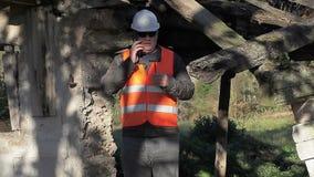Inspector de construcción que habla en el edificio dañado cerca abandonado del smartphone metrajes
