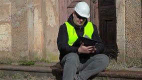 Inspector de construcción que sienta y que comprueba la documentación en el señorío viejo metrajes