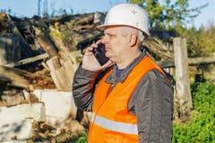 Inspector de la construcción que habla en el smartphone cerca abandonado, edificio dañado Fotos de archivo libres de regalías