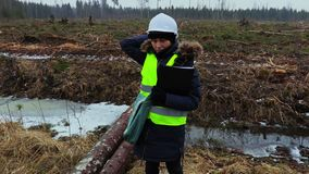 Inspector de sexo femenino de la silvicultura en el derribo del sitio en día de invierno lluvioso metrajes