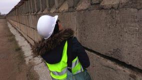 Inspector de sexo femenino que comprueba y que camina cerca del muro de cemento almacen de metraje de vídeo
