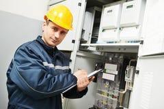 Inspector del electricista que controla datos del contador eléctrico Imágenes de archivo libres de regalías