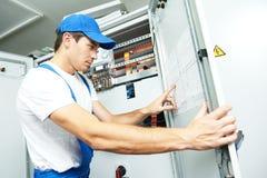 Inspector del ingeniero del electricista delante del fuseboard imágenes de archivo libres de regalías