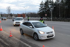 The inspector dorozhno-patrol service checks the documents of the driver of the car. Stock Images