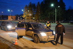The inspector dorozhno-patrol service checks the documents of the driver of the car. Royalty Free Stock Photography