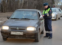 The inspector dorozhno-patrol service checks the documents of the driver of the car. SNEGIRI, RUSSIA - MARCH 14, 2014:The inspector dorozhno-patrol service Royalty Free Stock Photography