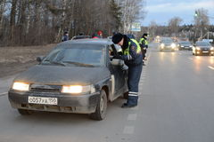 The inspector dorozhno-patrol service checks the documents of the driver of the car. Royalty Free Stock Image