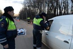 The inspector dorozhno-patrol service checks the documents of the driver of the car. SNEGIRI, RUSSIA - MARCH 14, 2014:The inspector dorozhno-patrol service Royalty Free Stock Image