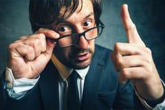 Inspector enojado del impuesto que parece serio, el amenazar del finger Fotografía de archivo