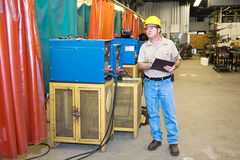 Inspector on Factory Floor. Inspector checking the welding equipment in a metal works factory Royalty Free Stock Image