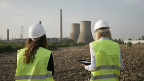 Inspector female engineers examining petroleum refinery installations using tablet pc on industrial area -. Inspector female engineers examining petroleum stock footage
