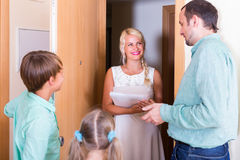 Inspector greeting family of new tenants Stock Photos