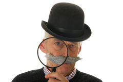 Inspector with magnifier. Portrait of a funny inspector with a big magnifier for investigation Stock Photo