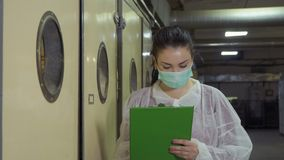 Inspector in protective overalls and mask check incubators at poultry farm. Inspector check incubator at poultry farm. Woman wearing protective mask and overalls stock footage