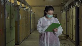 Inspector in protective overalls write report after checking incubators. Inspector check incubator at poultry farm. Woman wearing protective mask and overalls stock video footage