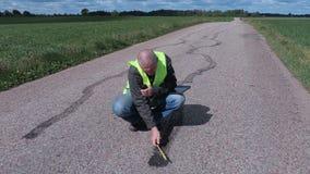 Inspector que usa cinta métrica cerca de marcas del neumático en el camino metrajes