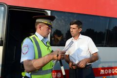 The inspector of the road police patrol checks documents from the driver of the intercity passenger bus. MOSCOW REGION, RUSSIA - AUGUST 3,2017: The inspector of Stock Photo