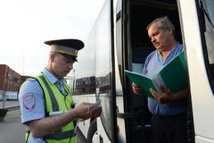 The inspector of the road police patrol checks documents from the driver of the intercity passenger bus. Moscow Region, Russia - August 3,2017: The inspector of Stock Photos
