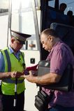 The inspector of the road police patrol checks documents from the driver of the intercity passenger bus. MOSCOW REGION, RUSSIA - AUGUST 3,2017: The inspector of Royalty Free Stock Photography