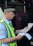 The inspector of the road police patrol checks documents from the driver of the intercity passenger bus. MOSCOW REGION, RUSSIA - AUGUST 3,2017:The inspector of Royalty Free Stock Photography