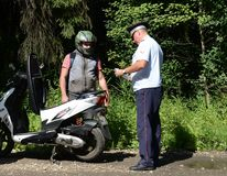 The inspector of the road police patrol checks the documents from the driver of the motorbike. MYTISHCHI, RUSSIA - AUGUST 12, 2017:The inspector of the road Stock Image