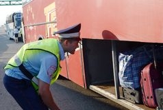 The inspector of the road police patrol checks the luggage compartment of the intercity passenger bus. MOSCOW REGION, RUSSIA - AUGUST 3,2017: The inspector of Stock Photography