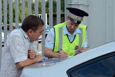An inspector of the road police patrol service makes a report on the violation of traffic rules. MOSCOW REGION, RUSSIA - AUGUST 3,2017: An inspector of the road Stock Photos
