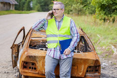 Inspector talking on smart phone near burned down car wreck on the side of the road Stock Photos