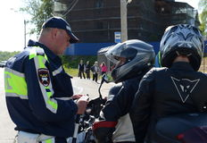 The inspector of traffic police checks the documents of the motorcycle. Stock Images
