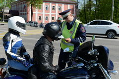 The inspector of traffic police checks the documents of the motorcycle. Royalty Free Stock Photo