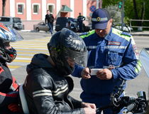 The inspector of traffic police checks the documents of the motorcycle. Stock Photos