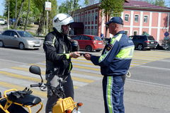 The inspector of traffic police checks the documents of the motorcycle. Stock Photography