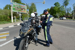 The inspector of traffic police checks the documents of the motorcycle. Royalty Free Stock Photos