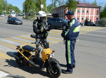 The inspector of traffic police checks the documents of the motorcycle. Royalty Free Stock Image