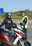The inspector of traffic police checks the documents of the motorcycle. Stock Photo