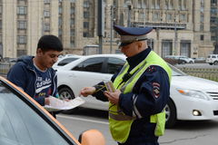The inspector of traffic police checks the documents of a taxi driver in Central Moscow. Royalty Free Stock Photography