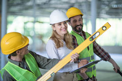 Inspector writing on clipboard while standing with workers holding level tool. Smiling inspector writing on clipboard while standing with workers holding level stock image