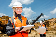 Inspectors in an open pit. Woman and a men working on a project in an open pit Royalty Free Stock Images