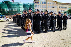 Inspectors patrol police handed the officer ranks in Uzhgorod. Uzhgorod, Ukraine - August 25. 2016: Girl passes near the policemans during the ceremony of Royalty Free Stock Image