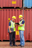 Inspectors standing containers. Harbor inspectors standing next to containers at depot Royalty Free Stock Images