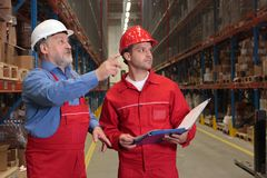 Inspectors in warehouse. Standing workers in uniforms with hardhats, reading invoice in warehouse. one is older , one is young stock photography