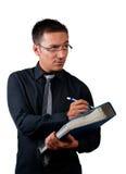 Inspektör med den svarta skjortan och band som rymmer en mapp och en penna Royaltyfria Foton