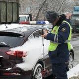 Inspektören av trafikpolisen gör protokollet på kränkning Royaltyfri Fotografi